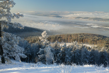 A view from the top of the mountain to a valley covered with fog in a frosty morning.