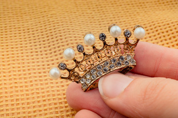 Model crown with pearls in hand