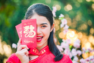Portrait chinese woman red dress traditional cheongsam in chinese temple.