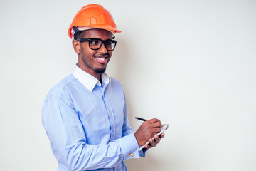architect designer black man African American holding paper drawing template.happy african builder painting house,businessman wears a helmet hard hat.young guy is painting sketch construction plan