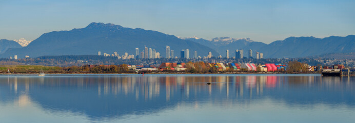 Panoramic view of cargoes at dock with colourful reflection on the river and city skyline and mountains at background at Richmond, BC Fototapete