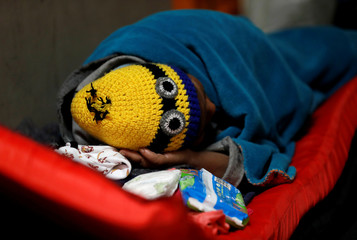 A migrant, part of a caravan of thousands traveling from Central America en route to the United States, sleeps at a shelter in Mexicali