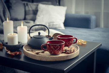 Two cups of tea on a serving tray on coffee table.