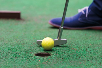 player makes a decisive blow in the game of mini golf