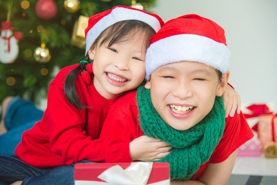 Young asian sibling,brother and sister smiling together at home with Christmas decoration