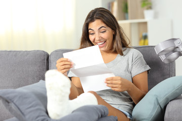 Excited disabled girl reading a paper letter at home