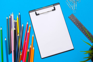 Clipboard and office supplies on blue background. Top view. Space for text