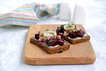 Smorrebrod, a traditional Danish open sandwich on rye bread with herring and pickled beets.