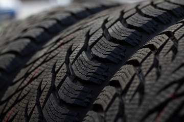 New winter tires during storage in stock. Tire treads removed close-up. Blackened new winter tires stored in stock.