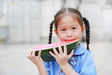 Cute little Asian child girl in school uniform enjoy eating fresh sliced watermelon.