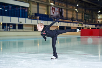 Full length portrait of little girl figure skating beautifully in indoor rink during competition or training, copy space