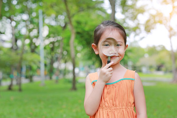 Portrait little Asian child girl looking through magnifying glass on park garden.