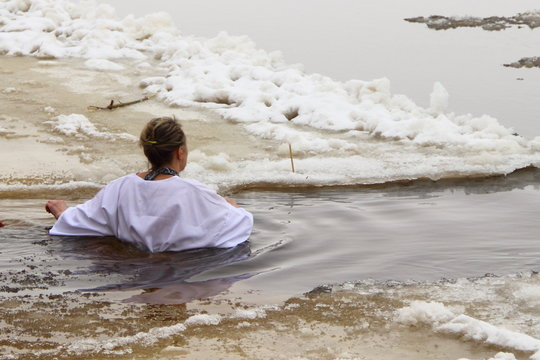 Woman in ritual white clothing swims in cold water outdoor - Faith, Christianity, baptism, religion, winter bathing ritual in the cross ice hole on the river among the ice floes