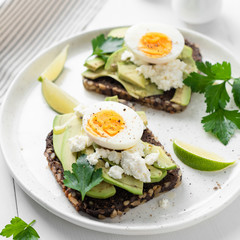 Toast with avocado, feta cheese and boiled egg on white plate, closeup view. Square crop. Avocado egg sandwich
