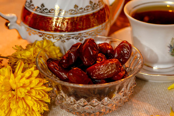Dates on wooden table with flowers and retro dishes with candle light in the dark room