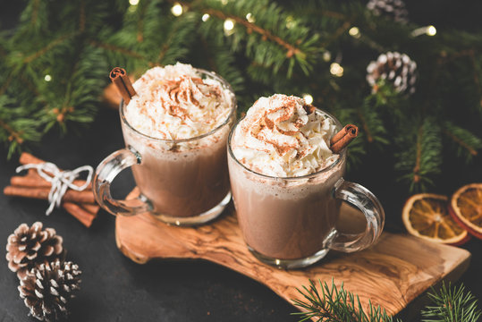 Two cups of hot chocolate with whipped cream and cinnamon on wooden serving board surrounded with fir tree, Christmas lights, cinnamon and pine cones. Cozy Christmas Drink