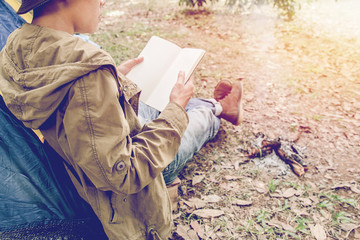 Asian young man sitting is reading a book in outside the tent. Alone camping in forest.
