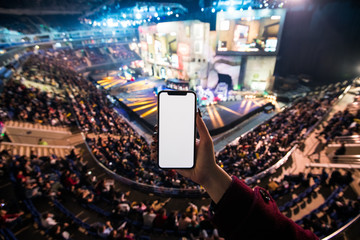 Woman's hands using digital application on the mobile smart phone at esport event at big arena. Copy space.