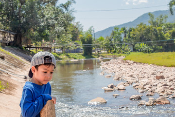 A boy wearing a hat standing water and rocks in a stream.