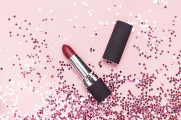Red lipstick and holographic glitter confetti in the form of stars on pink background Flat lay top view copy space. Makeup accessories, holiday winter decoration