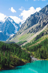 Keuken foto achterwand Alpen Creek from glacier flows into lake. Small fisherman in boat. Wonderful giant snowy mountains in sunlight. Azure water in mountain lake. Atmospheric beautiful landscape of highland nature in sunny day.