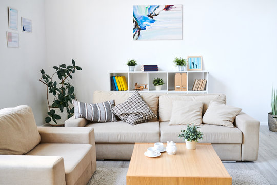 Modern interior of living room with abstract picture and certificates in frames on walls: comfortable sofa and armchair near coffee table