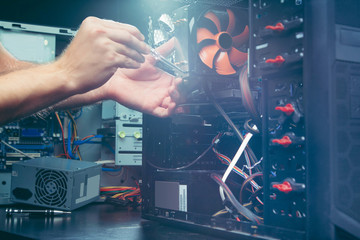 Technician repairing a computer, the process of replacing components on the motherboard. The technician hold the screwdriver for repairing PC. The concept of computer hardware, upgrade and technology
