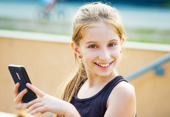 Smiling teenage girl in a black singlet holding smartphone in hands