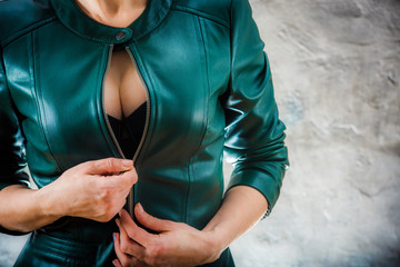 Big woman breast in leather jacket. Seductive girl showing her breast. Female decollete with sexy breast cleavage