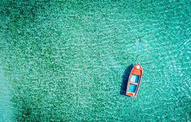 Aerial photo of a red lonely tboat tied up in crystal clear turquoise sea water