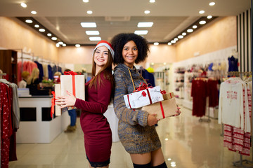 Two mixed race women with gift boxes in hands at store. Multi ethnic girls smiling with presents on christmas new year sale. Caucasian and african american females shopping presents for holidays.