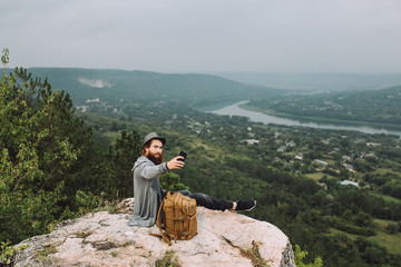 Young hiker man makes selfie on the background of the summer landscape.The guy has a long beard.Hiking and recreation theme.