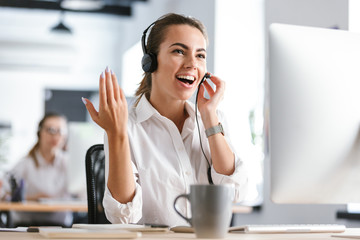 Emotional business woman in office callcenter working with computer wearing headphones.