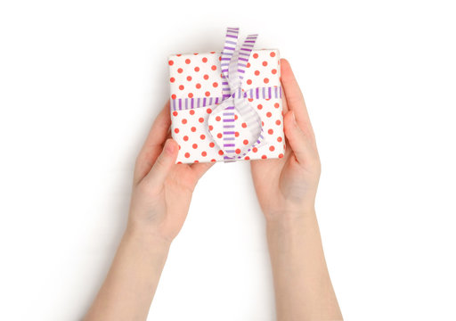 Little girl's hands holding small present isolated on a white background