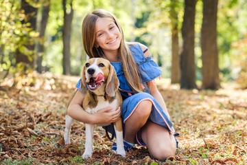 Little smiling blond girls sitting together hugging beagle dog in a sunshine autumn park