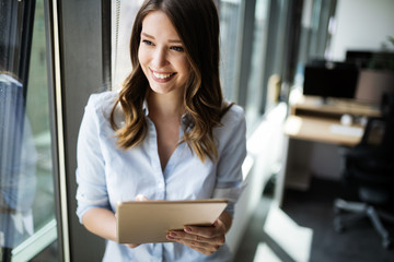 Wall Mural - Attractive businesswoman using a digital tablet while standing in front of windows