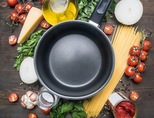 cooking vegetarian pasta with cherry tomatoes, parsley, onion and garlic, butter, tomato paste and cheese, the ingredients are laid out around the pan on a rustic wooden background