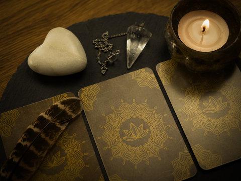 Wahrsagekarten mit Kerze, Pendel, Feder und Stein