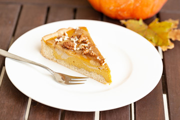 Vegan cheesecake infused with creamy pumpkin, silken tofu and cashews - decorated with pecan