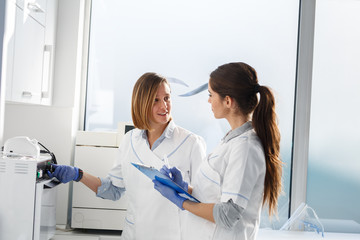Female dentists in dental office .They cleans equipment for next working day.Using autoclave.