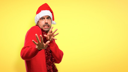 Man with red clothes celebrating the Christmas holidays is a little bit nervous and scared stretching hands to the front on yellow background