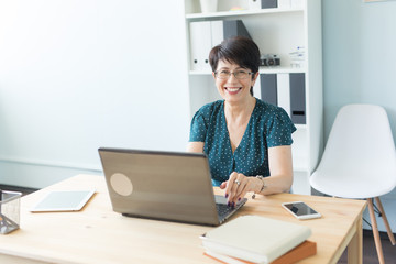Door stickers Wall Decor With Your Own Photos Business, technology and people concept - middle aged woman at work using a laptop and smile