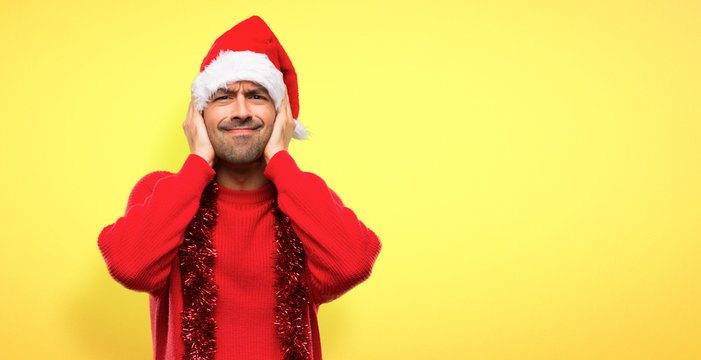 Man with red clothes celebrating the Christmas holidays covering both ears with hands on yellow background