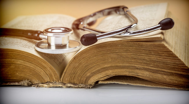 Stethoscope on an old book of medicine, conceptual image