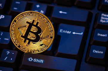 Gold coin bitcoin on the keyboard in blue from the monitor.