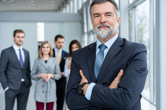 Businessteam in office, Happy Senior Businessman in His Office is standing in front of their team.