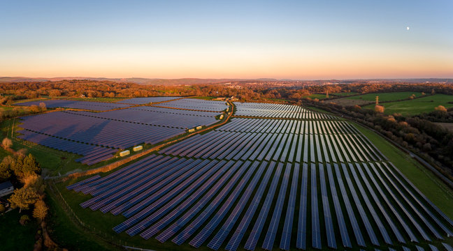 Aerial drone view of solar panels at a solar energy generation farm at Sunset in South Wales, UK