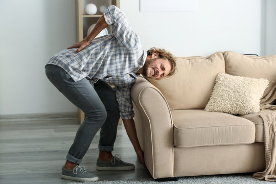 Young man suffering from back pain after carrying heavy furniture