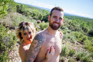 Young heterosexual couple poses naked in nature