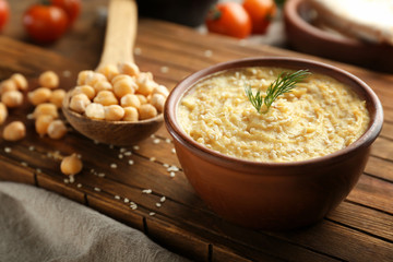 Bowl with tasty hummus on wooden board, closeup